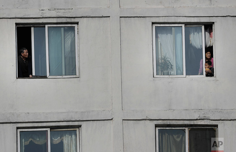 North Koreans watch runners of the Pyongyang marathon from their apartment windows on Sunday, April 9, 2017, in Pyongyang, North Korea. (AP Photo/Wong Maye-E)