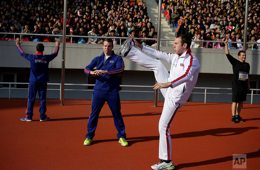 Foreigners dressed in North Korean tracksuits warm up ahead of the Pyongyang marathon at the Kim Il Sung Stadium on Sunday, April 9, 2017, in Pyongyang, North Korea. (AP Photo/Wong Maye-E)