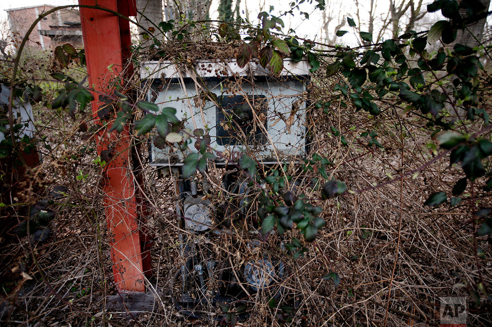 In this photo taken on Thursday, March 16, 2017, a petrol pump is surrounded by brambles, at the abandoned gasometer storage area, in Milan, Italy. (AP Photo/Luca Bruno)