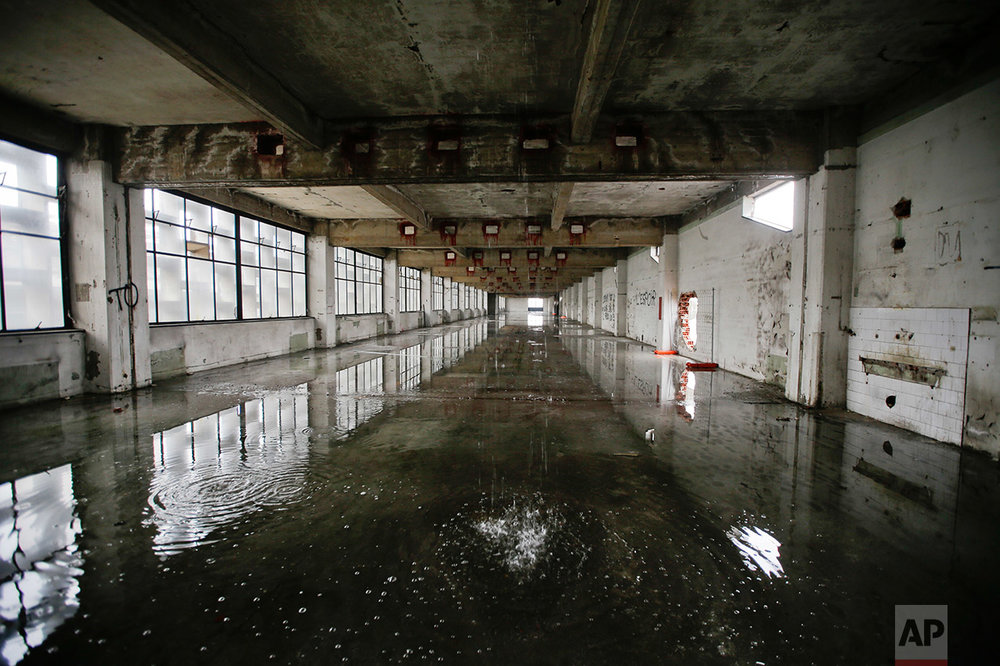 In this photo taken on Friday, Feb. 3, 2017, water comes from the roof inside the abandoned Alfa Romeo car factory, in Arese, near Milan, Italy, Friday, Feb. 3, 2017. (AP Photo/Luca Bruno)