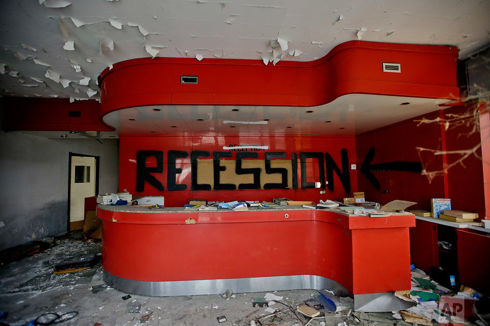 In this photo taken on Thursday, Nov. 3, 2016, the word 'recession' was written on the desk of the reception at the abandoned Hotel Americ in Carpiano, near Milan. (AP Photo/Luca Bruno)