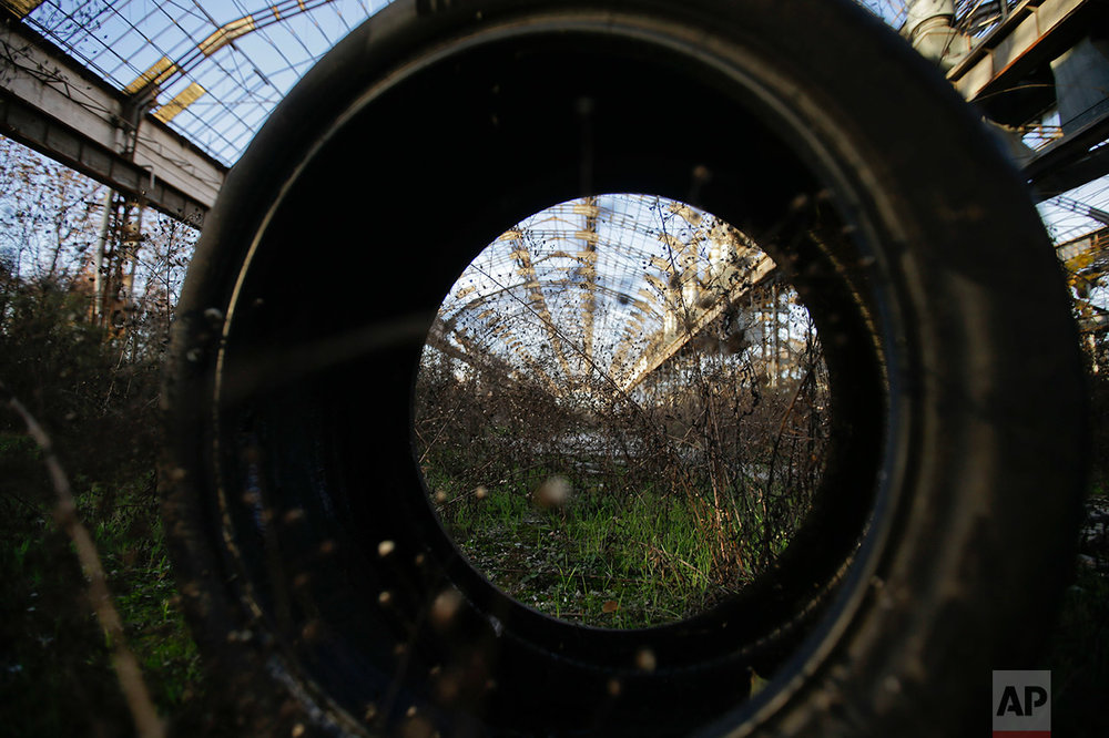 In this photo taken on Thursday, Dec. 1, 2016, a view through a tire of the abandoned automotive Innocenti factory in Milan, Italy. (AP Photo/Luca Bruno)