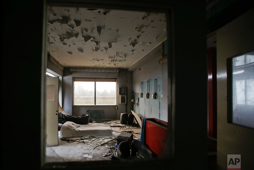 In this photo taken on Thursday, Nov. 3, 2016, a bed is leaning to the ground inside the former telephone room of the abandoned Hotel Americ in Carpiano, near Milan, Italy.  (AP Photo/Luca Bruno)