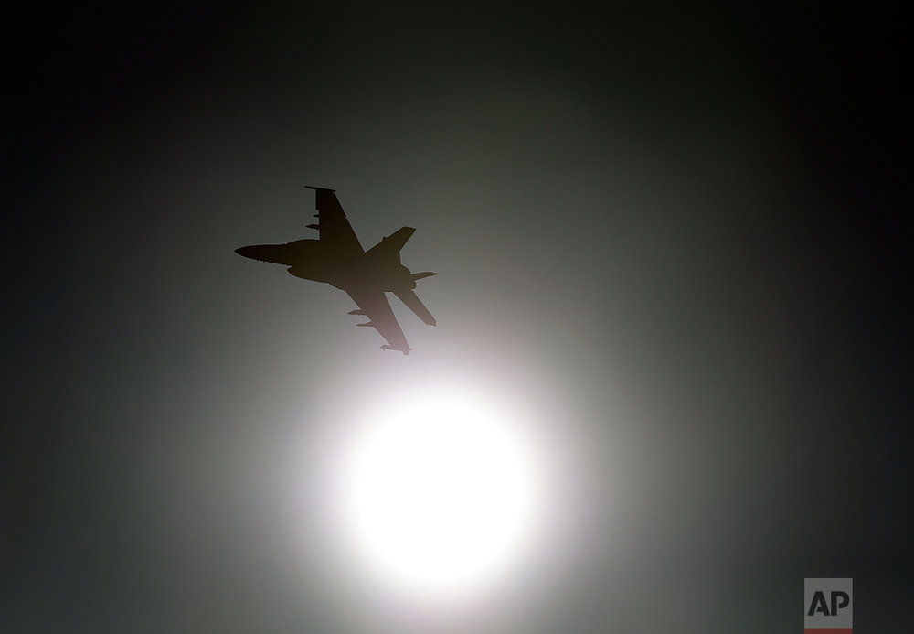 "In this Feb. 28, 2017, photo, Thomas ""Tom"" P. McGee of the VX-9 Vampire squadron from Naval Air Weapons Station China Lake, flies an F/A-18E Super Hornet toward the sun over Death Valley National Park, Calif. Military jets roaring over national parks have long drawn complaints from hikers and campers. But in California's Death Valley, the low-flying combat aircraft skillfully zipping between the craggy landscape has become a popular attraction in the 3.3 million acre park in the Mojave Desert, 260 miles east of Los Angeles. (AP Photo/Ben Margot)"