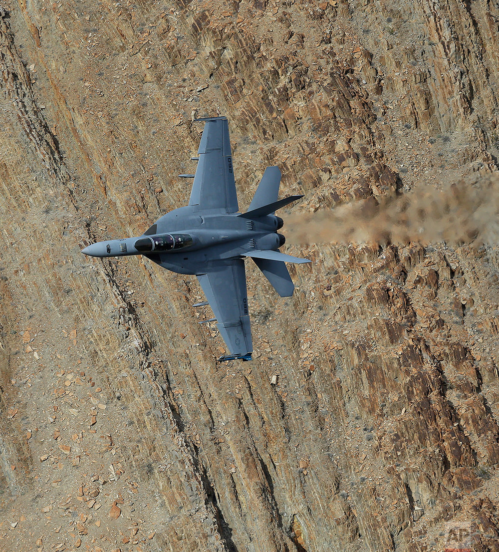 In this Feb. 27, 2017, photo, an F/A-18F Super Hornet from China Lake VX-9 Vampire squadron flies through the nicknamed Star Wars Canyon in Death Valley National Park, Calif. (AP Photo/Ben Margot)