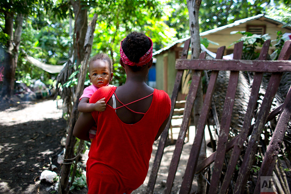 In this Aug. 15, 2016 photo, Janila Jean, 18, carries her daughter as she walks to her friend's house before an interview in Jacmel, Haiti. Jean said she was a 16-year-old virgin when a U.N. peacekeeper from Brazil lured her to the U.N. compound two years earlier with a smear of peanut butter on bread, then raped her at gunpoint and left her pregnant. (AP Photo/Dieu Nalio Chery)
