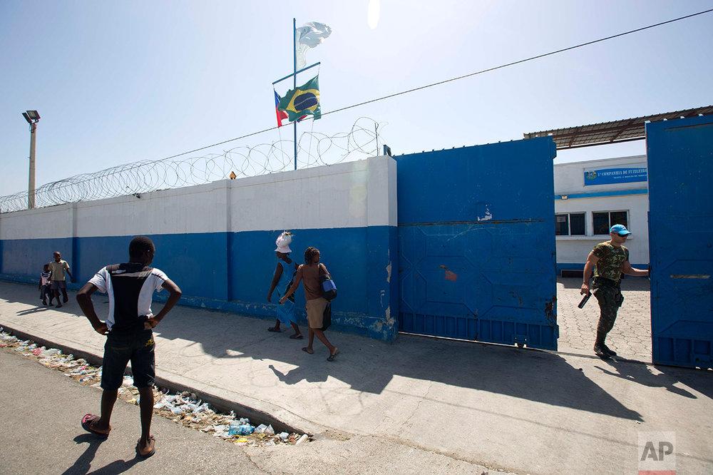 A Brazilian U.N. peacekeeper opens a gate at the U.N. base in the Cite Soleil slum of Port-au-Prince, Haiti. (AP Photo/Dieu Nalio Chery)