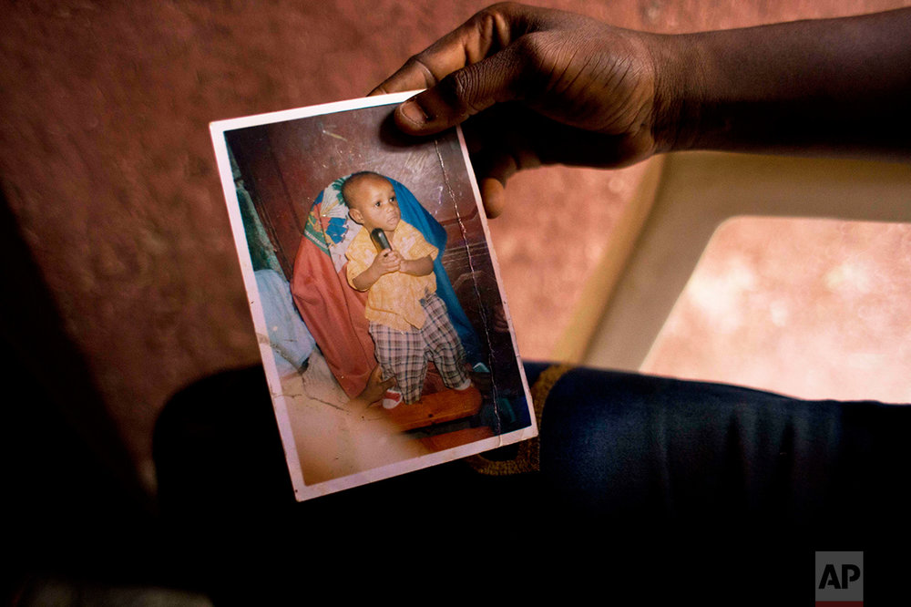 "In this Aug. 11, 2016 photo, Martine Gestime 32, holds up a picture of her son, Ashford, during an interview in Port-au-Prince, Haiti. Gestime said she was raped by a Brazilian peacekeeper in 2008 and became pregnant with Ashford. They live in a cramped two-room dwelling she shares with six other people in a Port-au-Prince slum. Unable to afford school for him, she relies on him to beg for food. ""He tells me all the time that he doesn't have a father or mother who can look after him."" (AP Photo/Dieu Nalio Chery)"