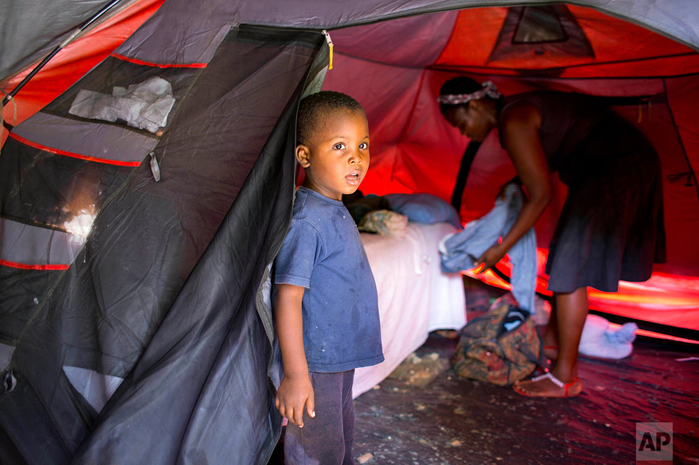 "In this Aug. 15, 2016 photo, Marlene Andre 38, background right, arranges clothes while her son, Johnsley, 5, stands in front of their tent in Jacmel, Haiti. Marlene was barely scraping by before a U.N. peacekeeper made her pregnant. The birth of her fourth child was the tipping point. She now can't afford rent and lives in a threadbare tent. ""In Haiti, we churn water to make butter. Life is hard."" (AP Photo/Dieu Nalio Chery)"