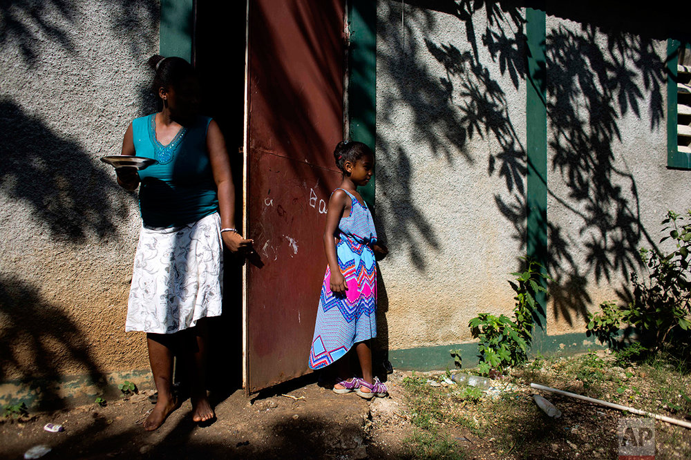 "In this Aug. 17, 2016 photo, Marie-Ange Haitis, 40, stands with her daughter, Samantha, at their home in Leogane, Haiti. Haitis says she met a Sri Lankan commander in December 2006 and he soon began making nighttime visits to her house. ""By January, we had had sex,"" she said. ""It wasn't rape, but it wasn't exactly consensual, either. I felt like I didn't have a choice."" Haitis says Samantha has started asking more questions about her father. (AP Photo/Dieu Nalio Chery)"