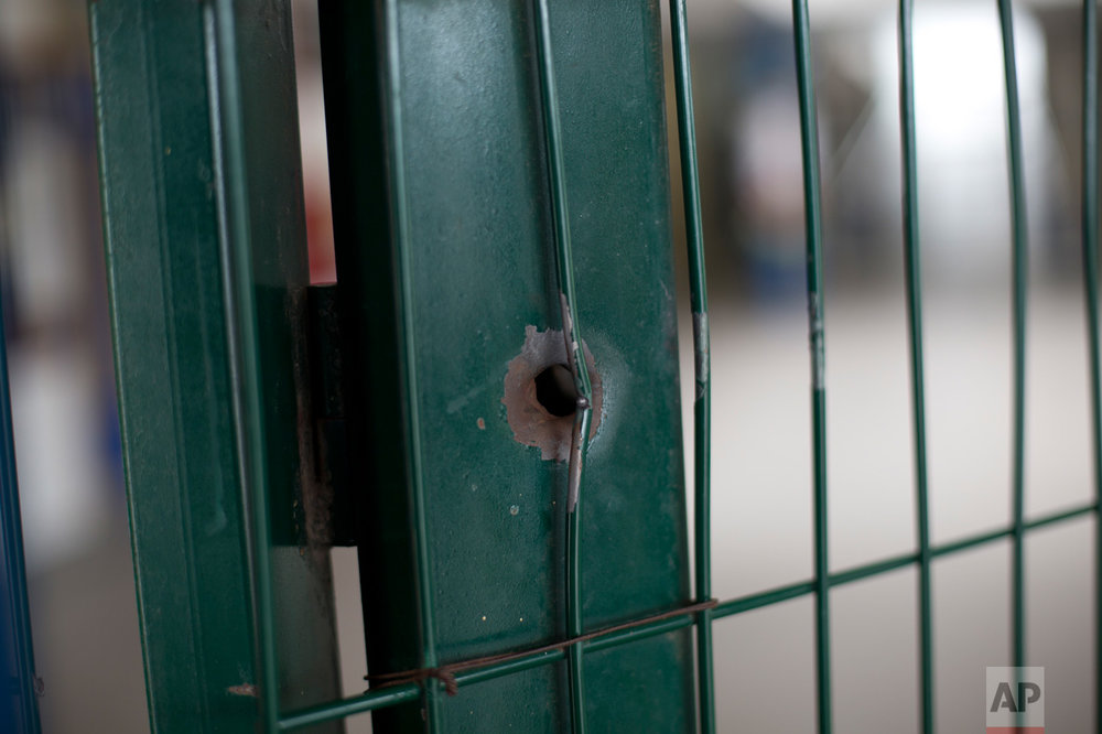This April 12, 2017 photo shows a bullet hole on the front gate of a school in Acari, Rio de Janeiro, Brazil, where 13-year-old Maria Eduarda Conceicao was shot and killed when she was caught in the crossfire of a lengthy shootout between police and gangsters. (AP Photo/Silvia Izquierdo)