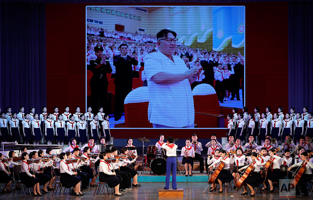 North Korean school children perform at the Mangyongdae Children's Palace while an image of their leader Kim Jong Un is projected on a screen Friday, April 14, 2017, in Pyongyang, North Korea.  (AP Photo/Wong Maye-E)