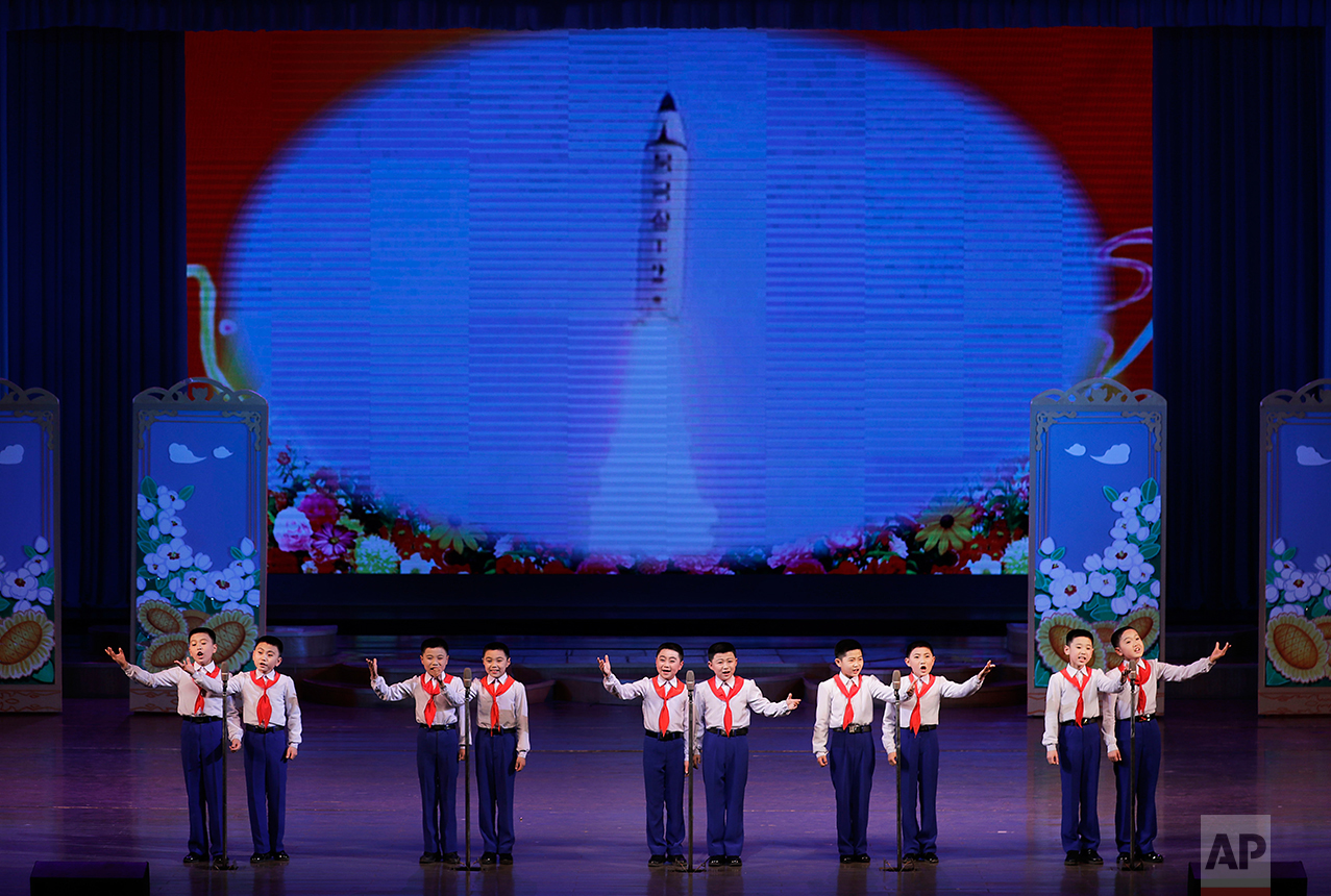 North Korean school children perform at the Mangyongdae Children's Palace while an image of a space launch vehicle is projected on a screen on Friday, April 14, 2017, in Pyongyang, North Korea. (AP Photo/Wong Maye-E)