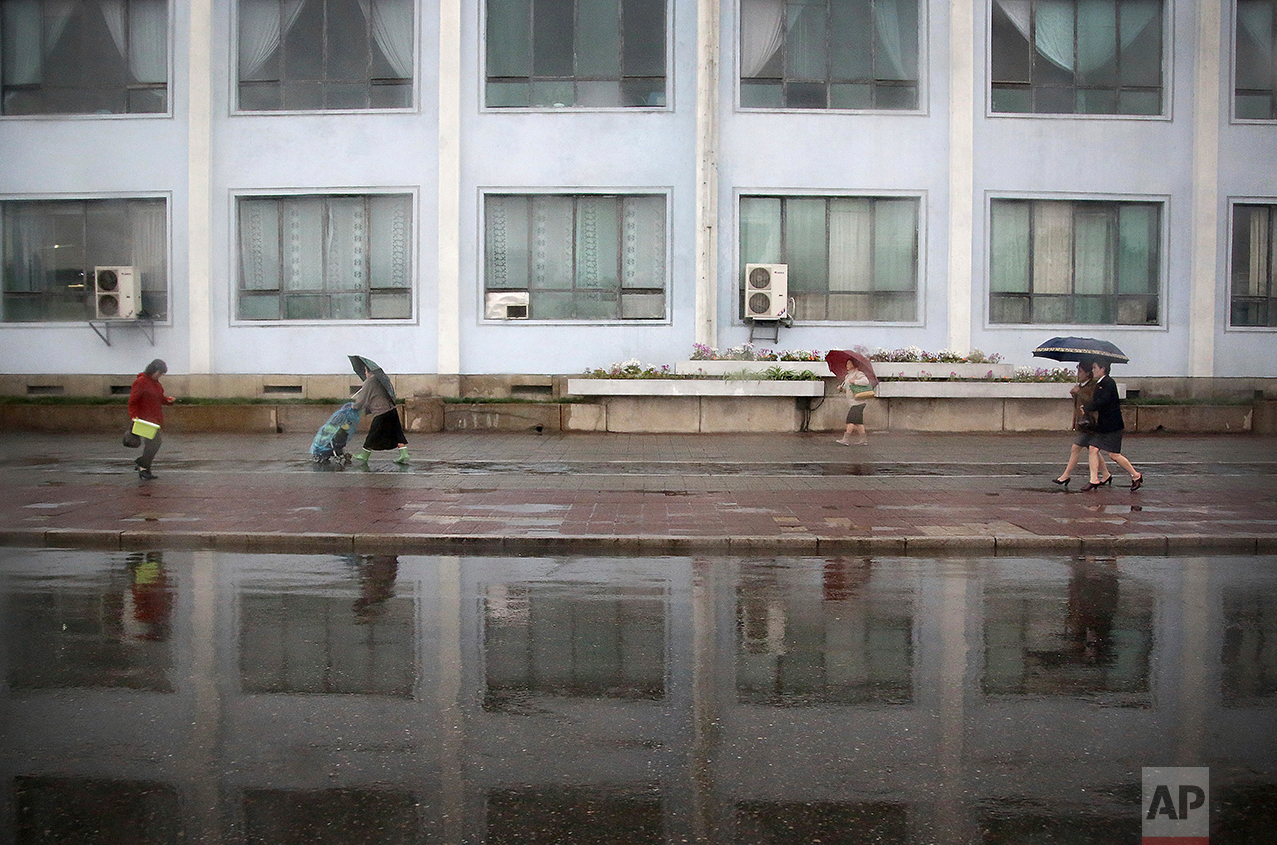 Pedestrians walk along a sidewalk on a rainy evening on Friday, April 14, 2017, in Pyongyang, North Korea. (AP Photo/Wong Maye-E)