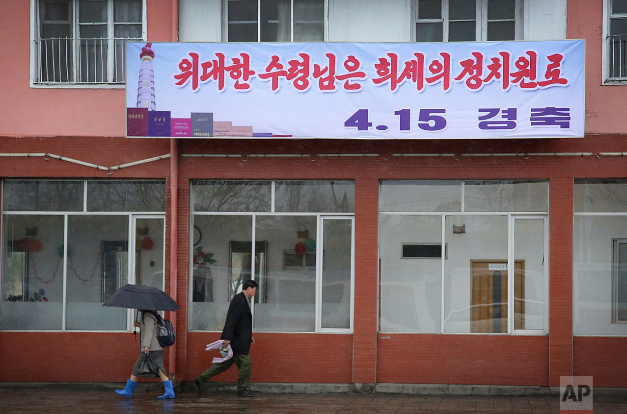 "Pedestrians walk in the rain beneath a sign which reads ""Great President, Extraordinary Political Veteran"" referring to late leader Kim Il Sung on Friday, April 14, 2017, in Pyongyang, North Korea. (AP Photo/Wong Maye-E)"