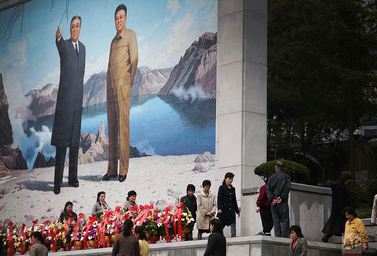 North Koreans offer flowers in front of a mural of late leaders Kim Il Sung, left, and Kim Jong Il on Friday, April 14, 2017, in Pyongyang, North Korea. (AP Photo/Wong Maye-E)