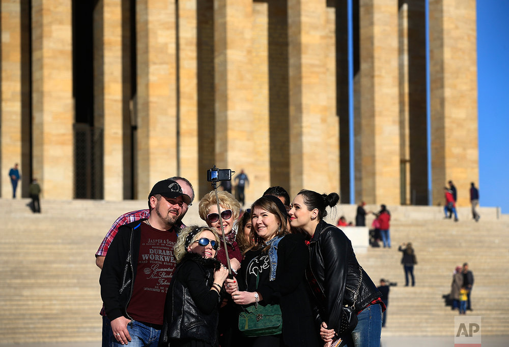 "In this March 29, 2017 photo, visitors pose for a photograph during a visit at the mausoleum of Mustafa Kemal Ataturk, the founder of modern Turkey in Ankara, Turkey. The legacy of the man whose surname means ""father of Turks"" was one of a modern, secular, western-leaning Turkey. But the personality cult that grew around him has very gradually been fading as current President Recep Tayyip Erdogan, in power since 2003 as alternately prime minister and president, has harked back to the glory days of the height of the Ottoman Empire to whip up patriotic sentiment. (AP Photo/Lefteris Pitarakis)"