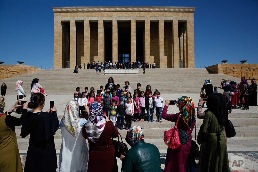 "In this March 29, 2017 photo, teachers take pictures of schoolchildren during a visit at the mausoleum of Mustafa Kemal Ataturk, the founder of modern Turkey in Ankara, Turkey. The legacy of the man whose surname means ""father of Turks"" was one of a modern, secular, western-leaning Turkey. But the personality cult that grew around him has very gradually been fading as current President Recep Tayyip Erdogan, in power since 2003 as alternately prime minister and president, has harked back to the glory days of the height of the Ottoman Empire to whip up patriotic sentiment. (AP Photo/Lefteris Pitarakis)"