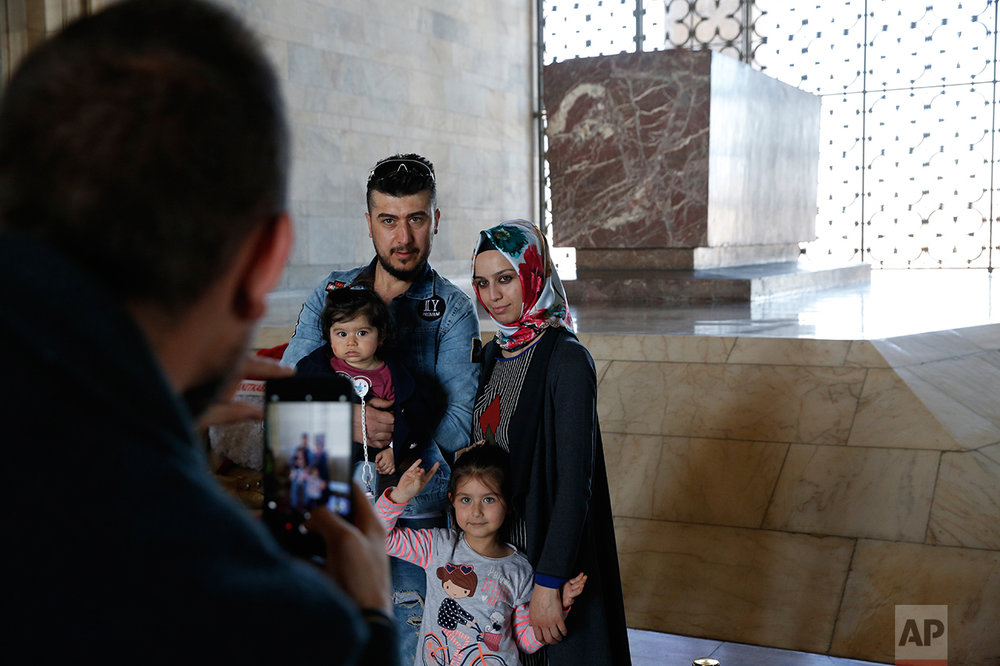 "In this March 29, 2017 photo, members of a family pose for a photograph during a visit at the mausoleum of Mustafa Kemal Ataturk, the founder of modern Turkey in Ankara, Turkey. The legacy of the man whose surname means ""father of Turks"" was one of a modern, secular, western-leaning Turkey. But the personality cult that grew around him has very gradually been fading as current President Recep Tayyip Erdogan, in power since 2003 as alternately prime minister and president, has harked back to the glory days of the height of the Ottoman Empire to whip up patriotic sentiment. (AP Photo/Lefteris Pitarakis)"