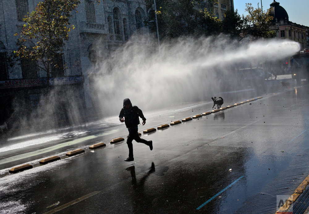 A demonstrator runs for cover as police fire a water cannon during a protest demanding education reform in Santiago, Chile, Tuesday, April 11, 2017. The demonstrators are demanding free access to school for all ages, including the university level. (AP Photo/Esteban Felix)