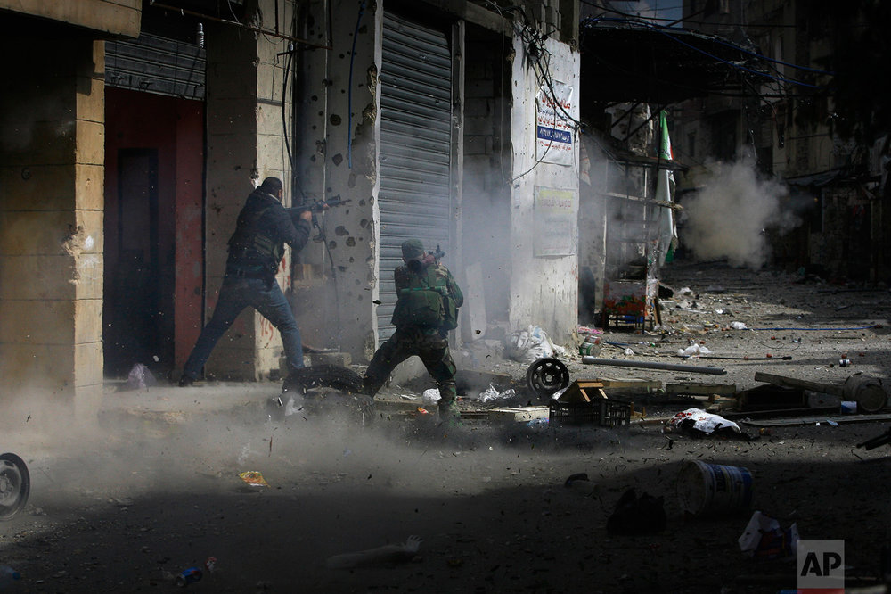 A member of the Palestinian Fatah Movement fires a rocket-propelled grenade during a clash that erupted between the Palestinian Fatah Movement and Islamists in the Palestinian refugee camp of Ein el-Hilweh near the southern port city of Sidon, Lebanon, Sunday, April 9, 2017. Ein el-Hilweh, the largest of 12 Palestinian refugee camps in Lebanon, is notorious for its lawlessness and is home to some extremists who sympathize with the Islamic State group and al-Qaida. (AP Photo/Mohammed Zaatari)
