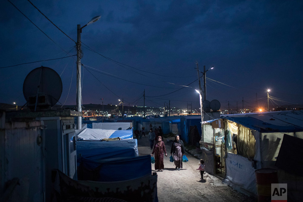 Syrian women walk through the Kawergosk refugee camp in northern Iraq, at dusk on Saturday, April 8, 2017. Millions of Syrian refugees are scattered across camps and illegal settlements across the region. (AP Photo/Felipe Dana)