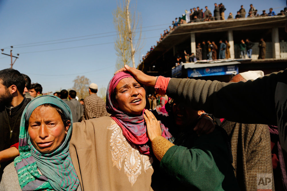 The mother, center, of Umer Farooq, a Kashmiri civilian who was killed Sunday, cries during his funeral in the village of Baroosa, 34 kilometers (21 miles) northeast of Srinagar, Indian-controlled Kashmir, Monday, April 10, 2017. Government forces opened fire on Sunday on crowds of people who attacked polling stations during a by-election for a vacant seat in India's Parliament, killing eight people. (AP Photo/Mukhtar Khan)