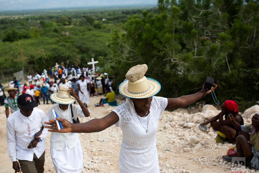 A woman stretches out her arms in prayer as she balances a stone on her head as a form of penance during a Good Friday ritual in Ganthier, Haiti, Friday, April 14, 2017. Thousands of Haitians flock to mount Calvaire Miracle, some with rocks balanced on their heads, to pray and seek renewal in one of the spiritually-steeped country's biggest annual pilgrimages. (AP Photo/Dieu Nalio Chery)