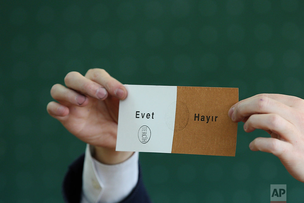 "A member of an electoral committee holds a ballot stamped in favor of ""Yes"" inside a polling station in Istanbul, on Sunday, April 16, 2017. (AP Photo/Emrah Gurel)"