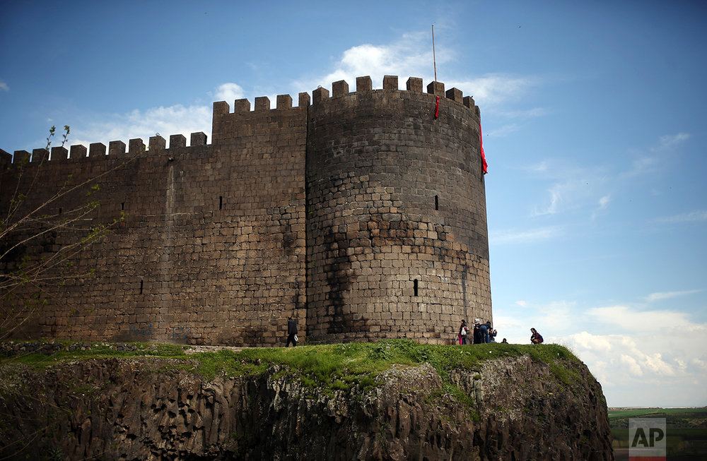 People walk past the Roman-era city walls in the historic Sur district of the mainly-Kurdish city of Diyarbakir, southeastern Turkey, Monday, April 17, 2017, one day after the referendum. Turkey's main opposition party urged the country's electoral board Monday to cancel the results of a landmark referendum that granted sweeping new powers to the nation's president Recep Tayyip Erdogan, citing what it called substantial voting irregularities. (AP Photo/Emre Tazegul)
