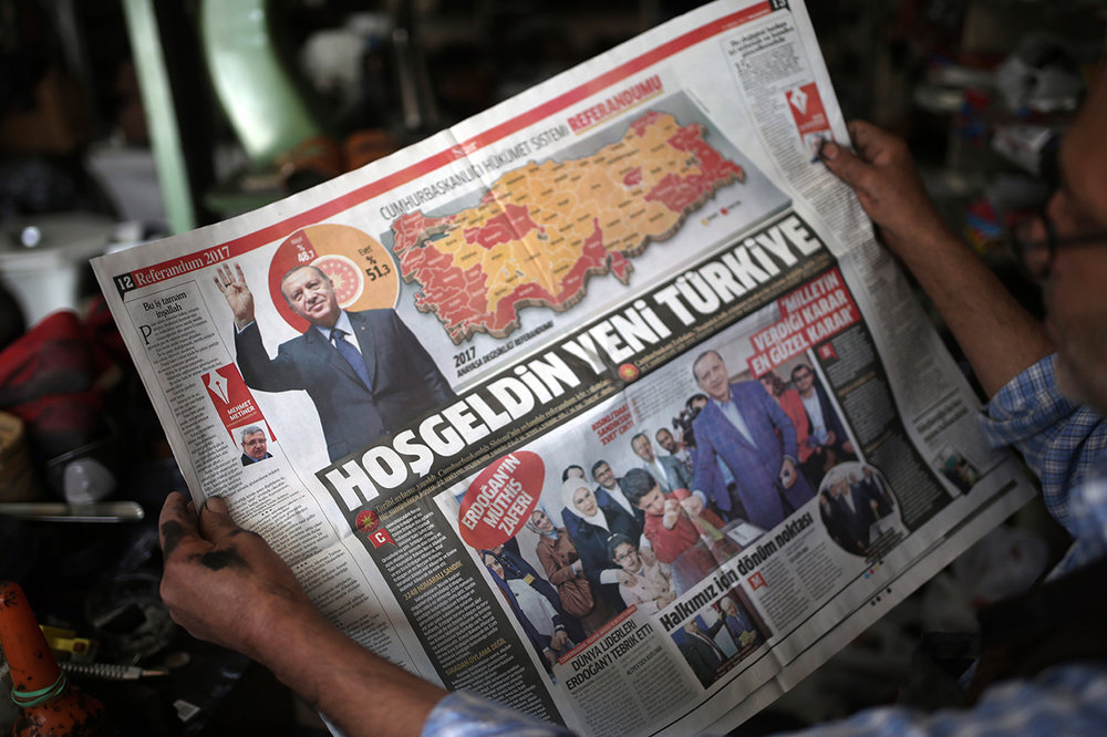 A man reads a newspaper with images of Turkey's President Recep Tayyip Erdogan and a map showing the results of Sunday referendum, in Diyarbakir, Turkey, Monday, April 17, 2017. Turkey's main opposition party urged the country's electoral board Monday to cancel the results of a landmark referendum that granted sweeping new powers to the nation's president, citing what it called substantial voting irregularities. (AP Photo/Emre Tazegul)
