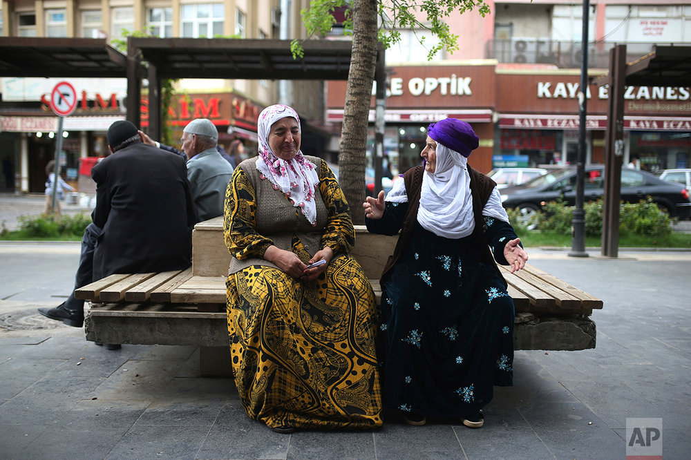 Two women chat as they sit in a boulevard in Diyarbakir, Turkey, Monday, April 17, 2017. Turkey's main opposition party urged the country's electoral board Monday to cancel the results of a landmark referendum that granted sweeping new powers to the nation's president, citing what it called substantial voting irregularities. (AP Photo/Emre Tazegul)