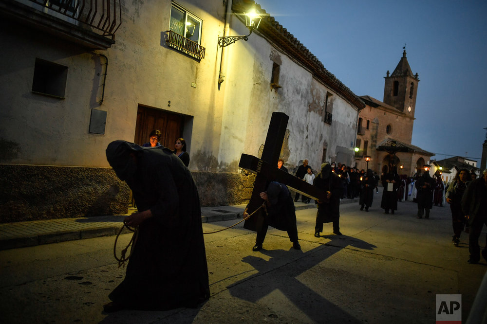 In this Thursday, April 13, 2017 photo, a penitent carries a cross taking part in the procession of ''El Ensogado'' during the Holy Week in Sietamo, northern Spain. (AP Photo/Alvaro Barrientos)