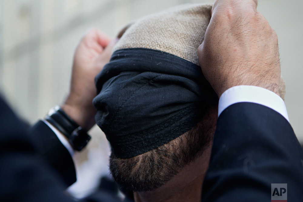 In this Thursday, April 13, 2017 photo, a 'Costalero' gets help to attach a sackcloth to protect his head before the start of a Holy Week procession during a Holy Week procession in Madrid, Spain. (AP Photo/Paul White)