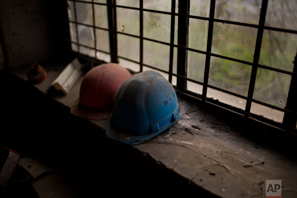 Helmets of former workers inside an inactive factory. (AP Photo/Emilio Morenatti)