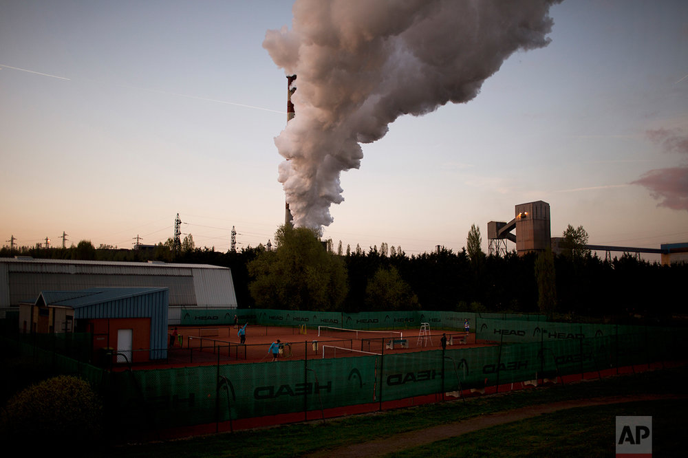 People play tennis at a private club as smoke rises from a chimney at a nearby factory. (AP Photo/Emilio Morenatti)