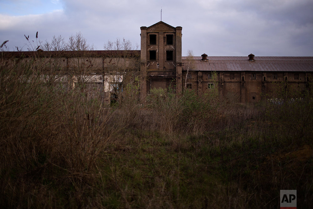 In this Wednesday April 5, 2017 photo, the main entrance of a former steel factory is covered by vegetation on the outskirts of Rombas, a french city located north east of France, near Hayange.  (AP Photo/Emilio Morenatti)