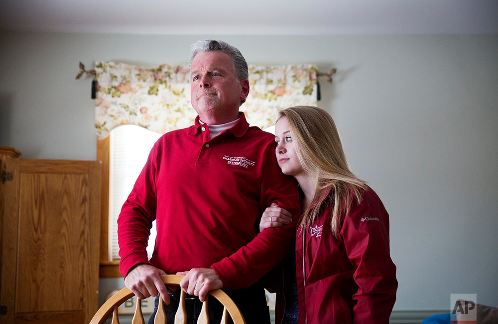 "Rick Rodrigue, left, stands with his daughter Stephanie, 17, at their home in Lewiston, Maine, Thursday, March 16, 2017. His daughter attends Lewiston High School where students speak dozens of languages, and hail from dozens of nations: Somalia, Djibouti, Congo, Yemen. ""It will help her in life,"" Rodrigue says. ""The world is not all white."" Yet in November 2016, Rodrigue voted for Donald Trump. Rodrigue's reasoning: America is struggling, and America needs to take care of its own before it takes care of anyone else. (AP Photo/David Goldman)"