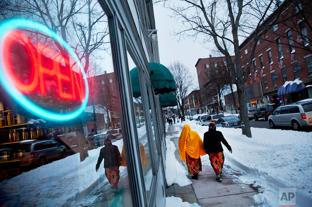 Women wearing traditional muslim head coverings walk past one of the many stores downtown owned by African refugees who have settled in Lewiston, Maine, Friday, March 17, 2017. AP Photo/David Goldman)