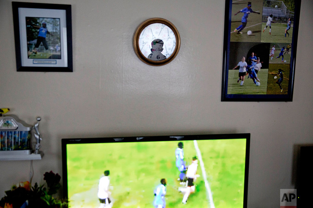 "Abdiaziz Shaleh, 19, a Lewiston high school senior and co-captain of the soccer team is reflected in a clock while watching soccer highlight on television at a friend's house in Lewiston, Maine, Tuesday, March 14, 2017. Shaleh, whose family is from Somalia, waited with them for several years in a refugee camp in Kenya before coming to the United States and eventually settling in Lewiston. Shaleh said President Trump's election has created fear in the refugee community, including among the many students who come from immigrant families. Shaleh also worries about the many refugees who are suffering in Somalia and other parts of Africa, where famine remains a huge issue. ""We got that chance (to come to America),"" he said. ""I just wanted them to have the same chance."" (AP Photo/David Goldman)"