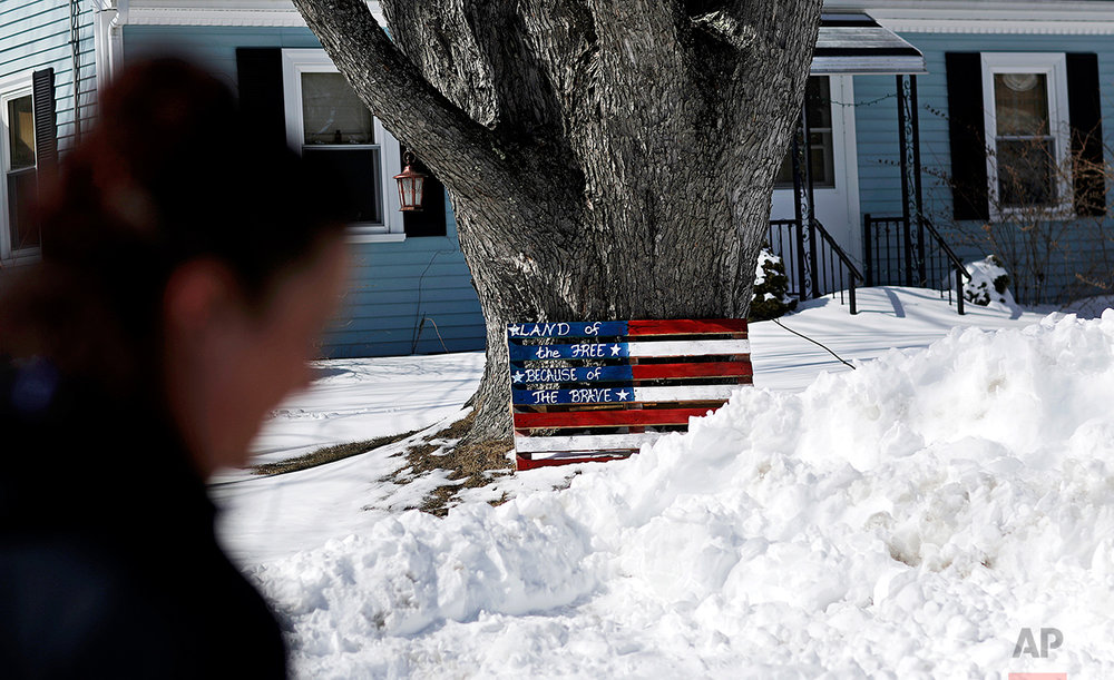 "Tabitha Beauchesne walks past a painted U.S. flag outside a neighbor's home in Auburn, Maine, Thursday, March 16, 2017. ""We have thousands and thousands of homeless people, we've got veterans out on the streets, and we're expected to bring in more refugees,"" said Beauchesne. ""We just need to stop."" Beauchesne voted for Barack Obama twice. Then she voted for Trump. (AP Photo/David Goldman)"