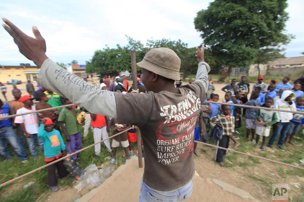 In this Sunday, March 11, 2017 photo, a referee invites young boys into the boxing ring in Chitungwiza, Zimbabwe. (AP Photo/Tsvangirayi Mukwazhi)