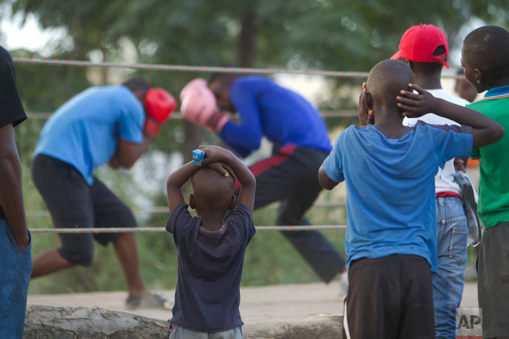 In this Sunday, March 18, 2017 photo, children follow a boxing match in Chitungwiza about 30 kilometres south east of Harare. i(AP Photo/Tsvangirayi Mukwazhi)
