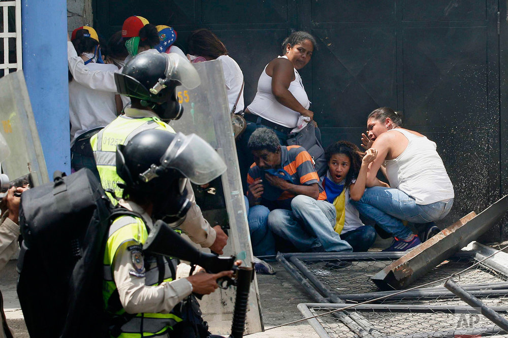 Anti-government demonstrators take cover from advancing Bolivarian Police officers during protests in Caracas, Venezuela, on Wednesday, April 19, 2017. Opponents of President Nicolas Maduro called on Venezuelans to take to the streets in marched against the embattled socialist leader. (AP Photo/Ariana Cubillos)