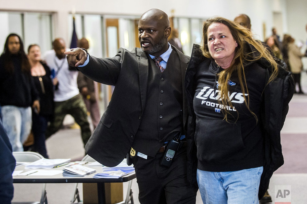 Flint police Officer Kristopher Jones removes resident Leah Palladeno, in handcuffs, from a town hall meeting at House of Prayer Missionary Baptist Church, related to the city's crisis with lead-tainted water, in Flint, Mich., on Thursday, April 20, 2017. Police say six people were arrested for disorderly conduct or other reasons. The event was held after Flint Mayor Karen Weaver reversed course Tuesday and recommended that Flint continue getting its drinking water from a Detroit-area system long term instead of a new pipeline. (Jake May/The Flint Journal-MLive.com via AP)