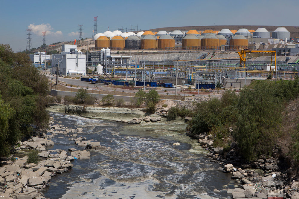 In this March 17, 2017 photo, a river of untreated sewage flows past the $530 million wastewater treatment plant in Atotonilco de Tula, Hidalgo state, Mexico. After years of delays, the plant, billed as the largest of its kind in Latin America, is in its testing phase and expected to come online later this year. (AP Photo/Rebecca Blackwell)