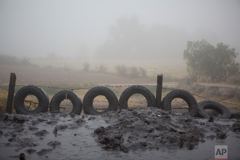 In this March 17, 2017 photo, tires protect a field from a thick layer of mud ejected from an adjacent irrigation canal when high flow creates a 30-foot spray, near the Endho reservoir, Hidalgo state, Mexico. Today, a vast network of low-tech, gravity-based canals irrigates more than 90,000 hectares (220,000 acres) of the Mezquital Valley with wastewater. Communities in other Mexican states have followed Hidalgo's example, and begun using sewage for farm irrigation. (AP Photo/Rebecca Blackwell)