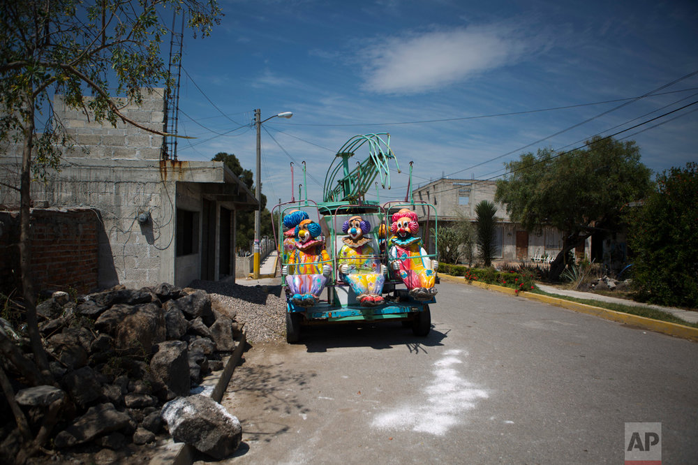 "In this April 1, 2017 photo, a fairground ride sits parked between partially-constructed homes in the village of Tenhe, near Mixquiahuala, Hidalgo state, Mexico. Farmers say the ""aguas negras"" have allowed them to educate their children and raise their own standard of living. Without government support, they say agriculture in the region could become unsustainable after the new wastewater treatment plant opens and spur migration to the United States and elsewhere in Mexico. (AP Photo/Rebecca Blackwell)"