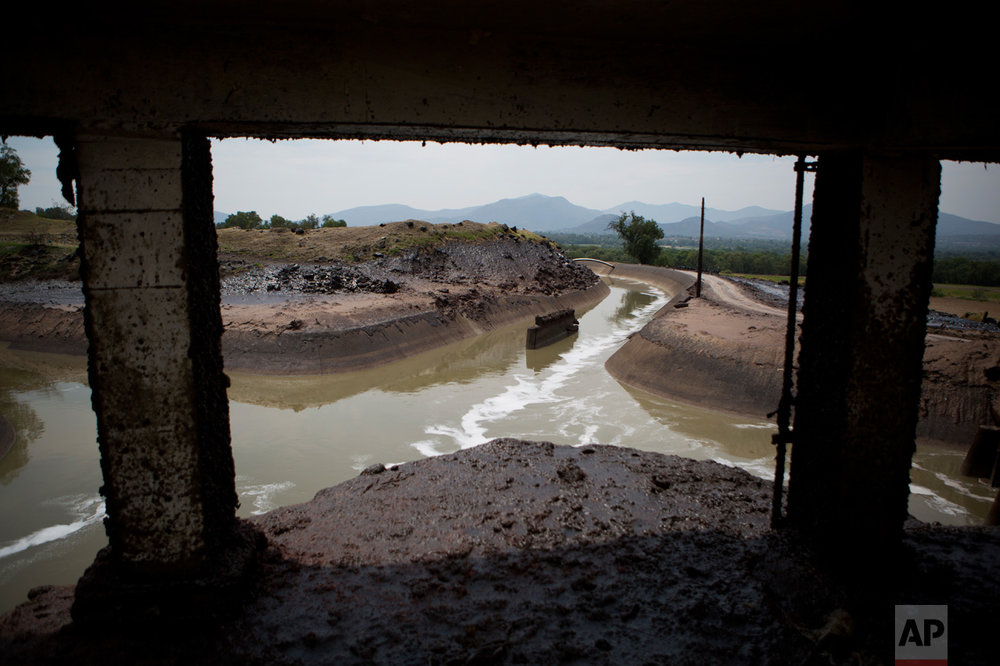 "In this March 31, 2017 photo, a thick layer of mud coats the earth around an irrigation canal where high flow in rainy season creates a 30-foot-high spray, near the Endho reservoir, Hidalgo state, Mexico. In brochures promoting the new wastewater treatment plant, the National Water Commission called the use of untreated sewage for farming ""a public health problem"" and a source of environmental pollution. (AP Photo/Rebecca Blackwell)"