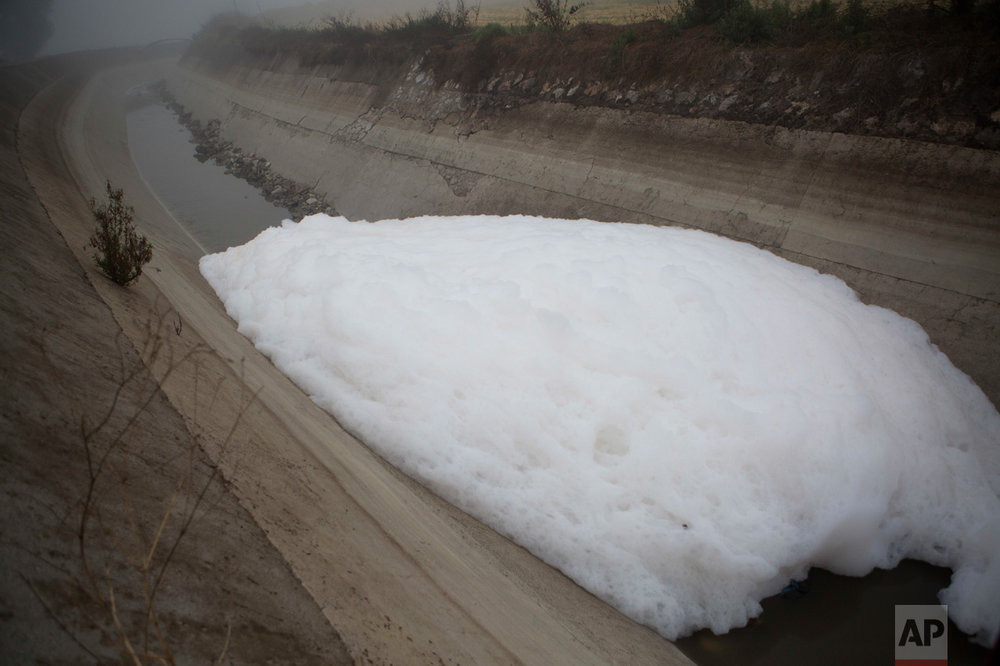 In this March 17, 2017 photo, foam from household detergents rests atop wastewater in an irrigation canal near the Endho reservoir in Tula, Hidalgo state, Mexico. Although the farmers are reluctant to lose the organic content in their black waters, they would support removing the contaminants which bother them more: heavy metals, industrial chemical pollution, detergents, and oils. The new wastewater treatment plant won't intentionally remove heavy metals or industrial chemical pollution, but many of the metals should remain in the sediments extracted inside the plant. (AP Photo/Rebecca Blackwell)